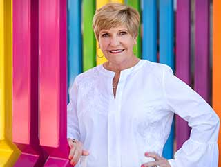 Mayor Betsy Price smiling at camera in front of colorful wall