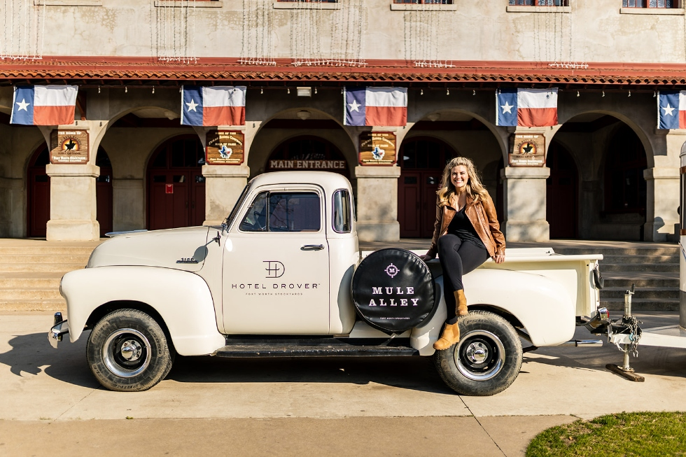 Michelle sitting on a vintage white pickup at the Hotel Drover